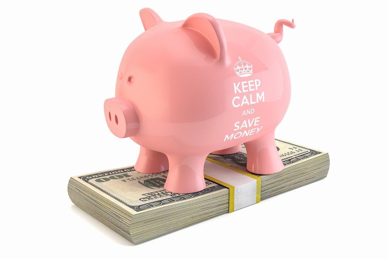 札束の上に乗った豚の貯金箱